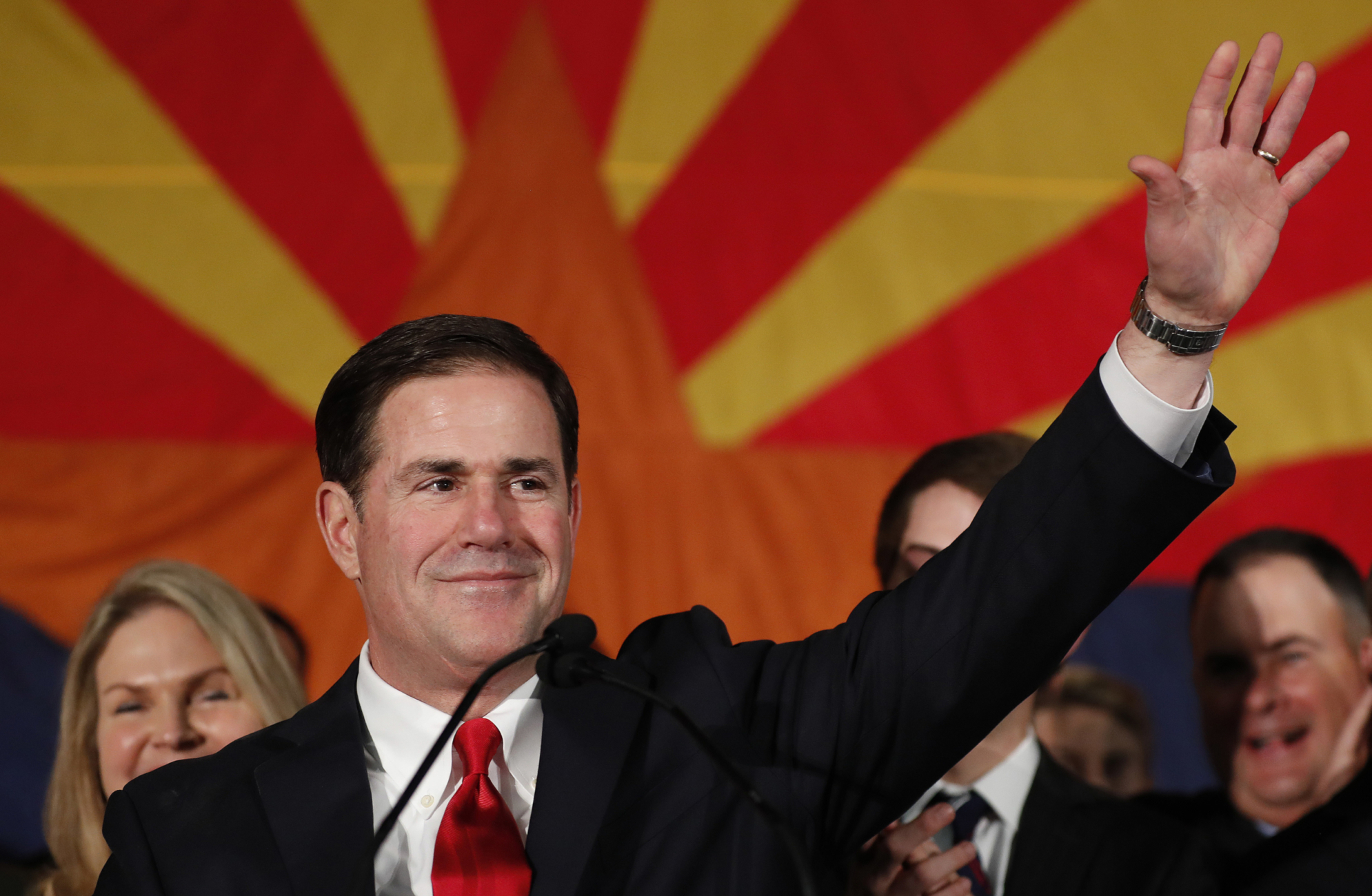 arizona governor doug ducey waving with the state flag of arizona in the background